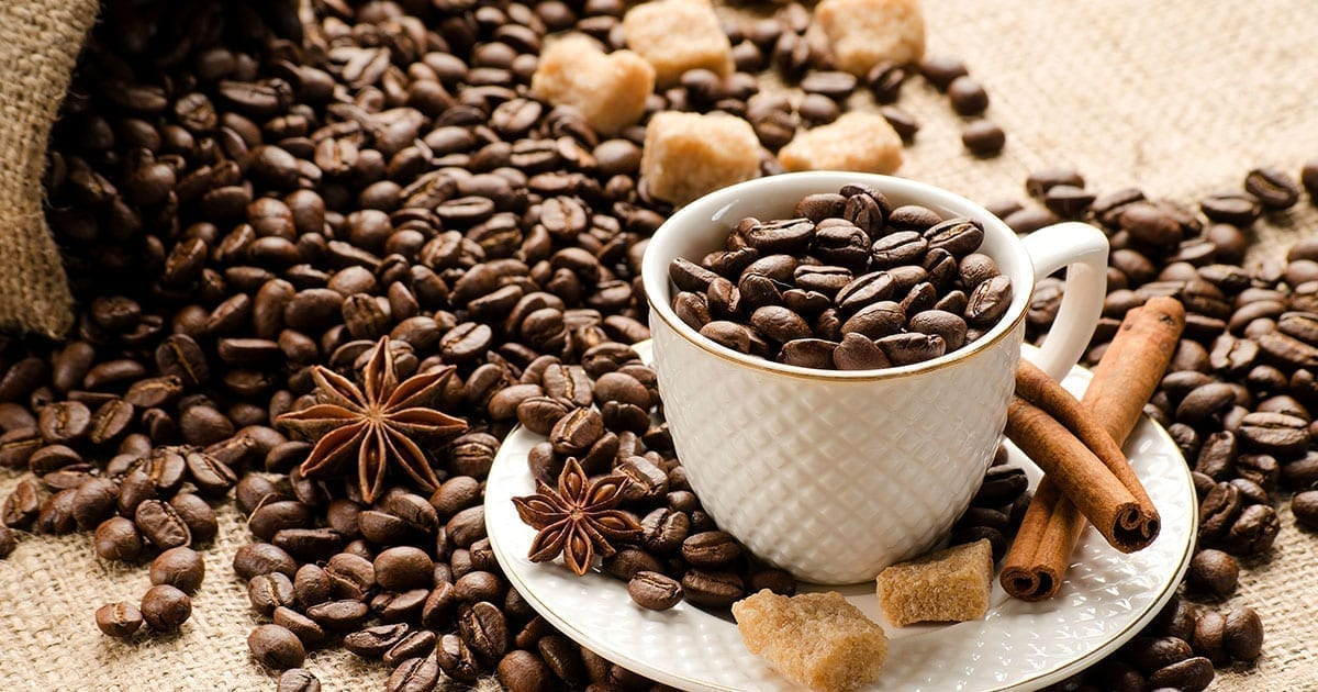 Coffee beans spilled on a table in a white coffee cup